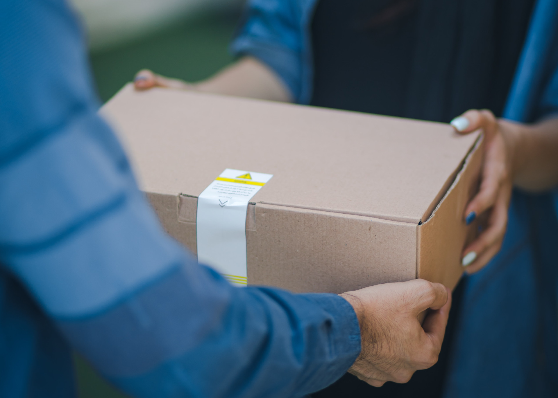 Someone delivering another person a box